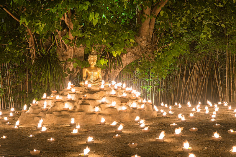 Velas do fogo da monge budista à Buda com reflexão bonita da água em Phan Tao Temple, Chiangmai, Tailândia fotografia de stock royalty free
