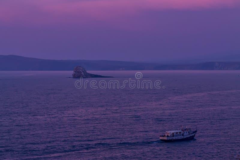 Velas do navio em um fundo do céu roxo do por do sol nas ondas do Lago Baikal de Olkhon fotografia de stock