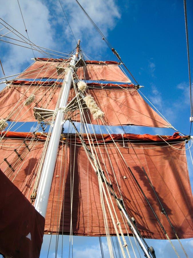 Velas e equipamento que penduram do mastro de um barco de navigação velho imagem de stock