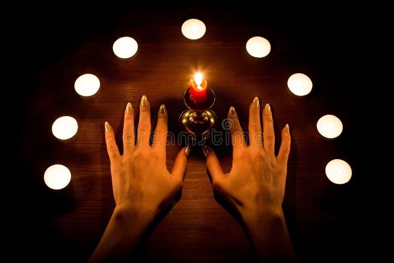 Velas e mãos fêmeas com os pregos afiados na superfície de madeira Adivinhação e feitiçaria, baixa chave fotografia de stock royalty free