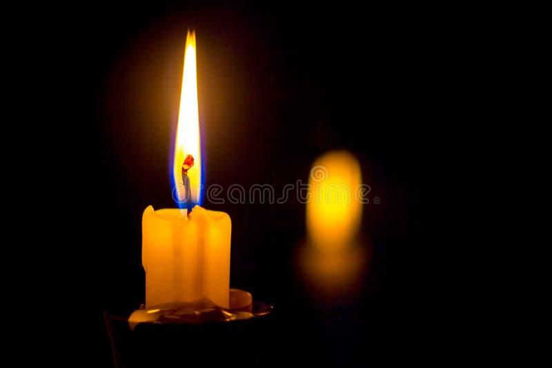 Velas en la palmatoria, qué combustión nuclear con el fuego brillante, en un bla imagen de archivo libre de regalías