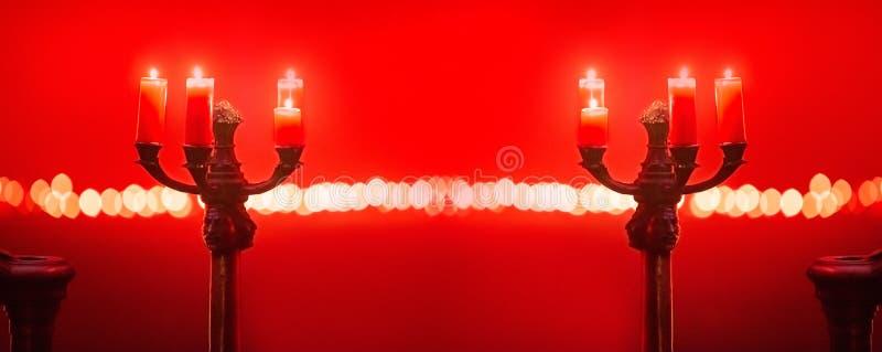Velas en tenedor de la palmatoria en sitio rojo fotografía de archivo libre de regalías