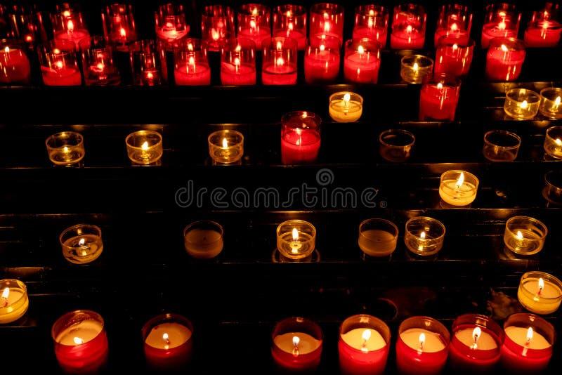 Velas encendidas blancas y rojas en iglesia en oscuridad imagen de archivo libre de regalías