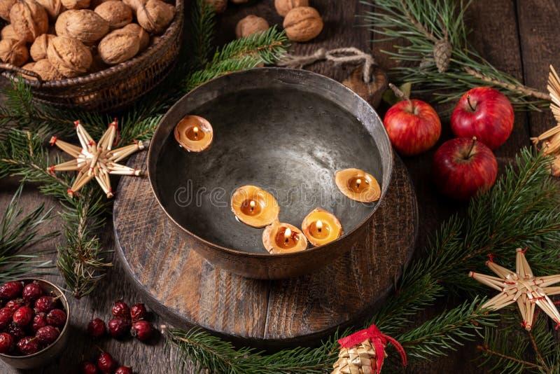 Velas feitas de cascas de nozes flutuando em uma tigela de água - velho costume de Natal fotos de stock