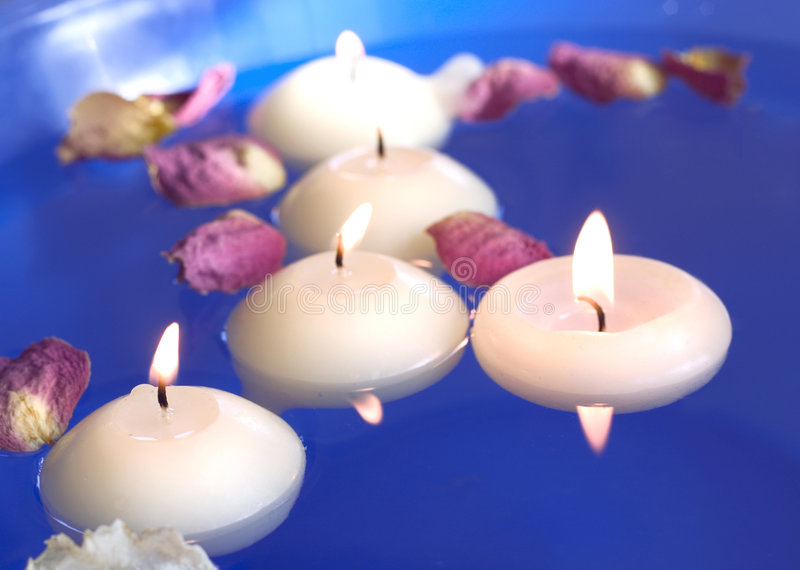 Velas flotantes con los pétalos color de rosa fotografía de archivo libre de regalías