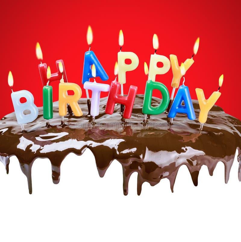 Velas iluminadas em seu aniversário em um bolo de aniversário fotografia de stock