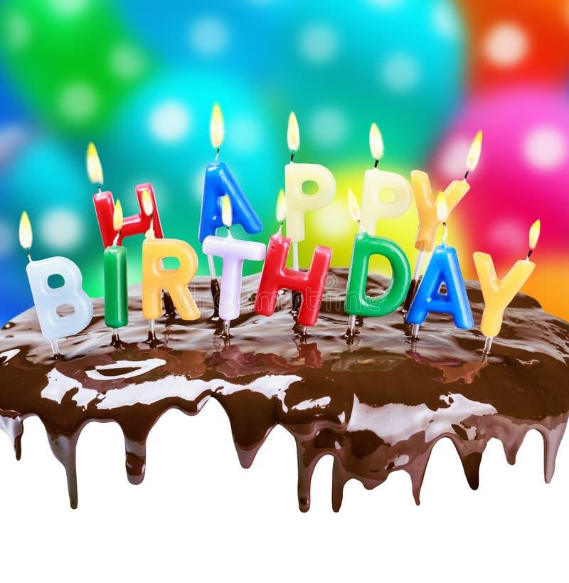 Velas iluminadas em seu aniversário em um bolo de aniversário imagens de stock royalty free