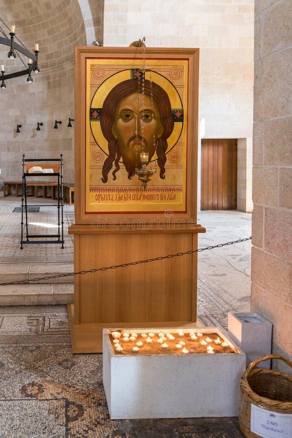 Velas iluminadas na frente do ícone Jesus Christ no salão central em Tabgha - multiplicação da igreja Católica do pão e dos peixe fotos de stock