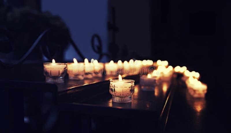 Velas iluminadas na igreja na tabela no fundo da reflexão da cruz foto de stock