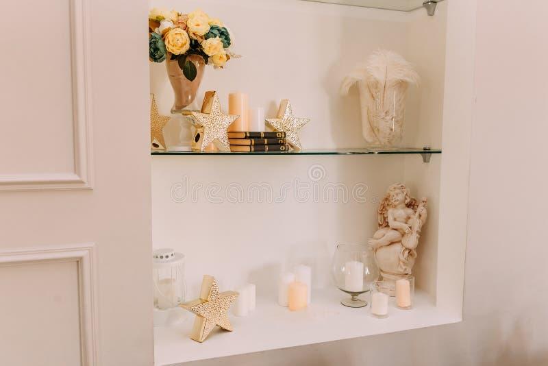 Velas, livros e estatuetas nas prateleiras imagens de stock