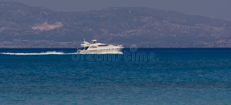 Velas más allá en de la distancia, Creta Grecia del barco de motor imagen de archivo