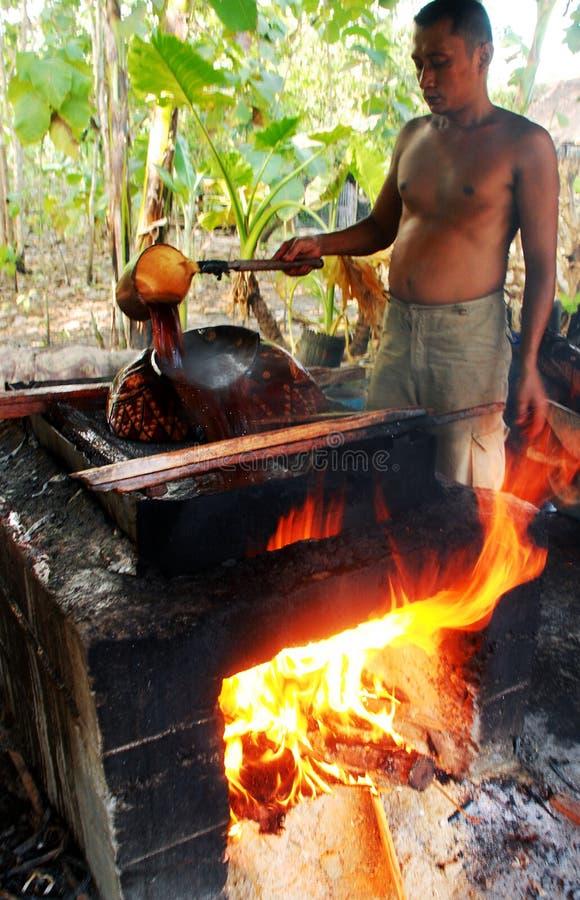 Velas manualmente de cessão em produtos de madeira do batik em fogões com água a ferver imagens de stock