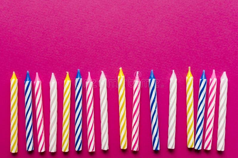 Velas multicoloras para la torta en el fondo de papel imagen de archivo libre de regalías