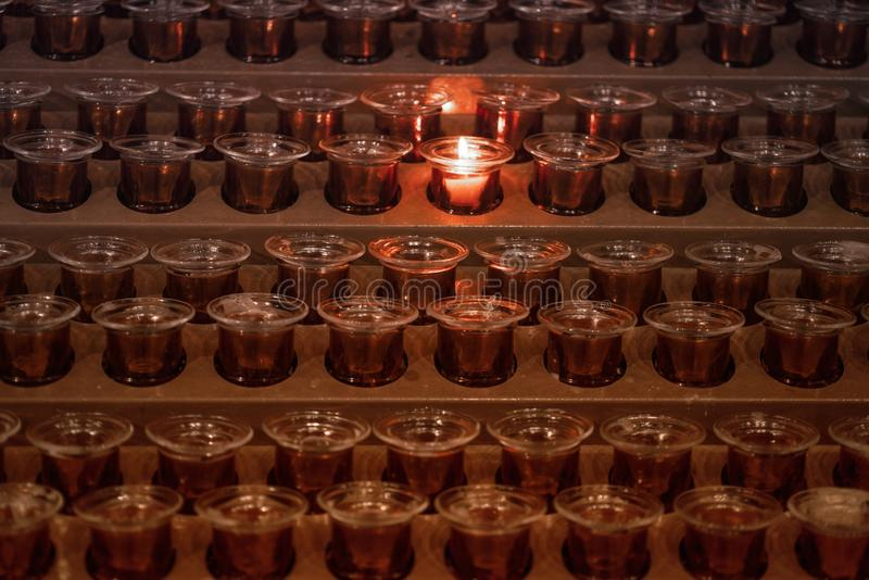 Velas na igreja Muitas chamas de vela que incandescem na obscuridade fotos de stock royalty free