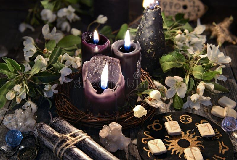 Velas negras con las runas, el círculo del zodiaco y las flores de la primavera fotografía de archivo