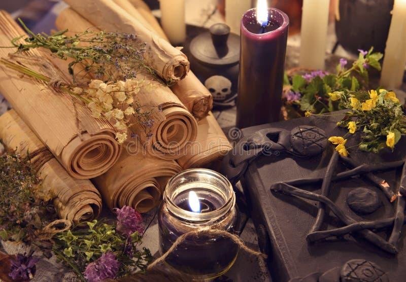 Velas pretas com pergaminhos velhos e o livro mágico mau com pentagram na tampa imagens de stock