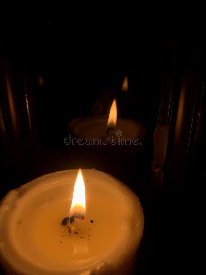 Velas que queimam-se na noite Velas brancas que queimam-se na obscuridade com imagem de stock