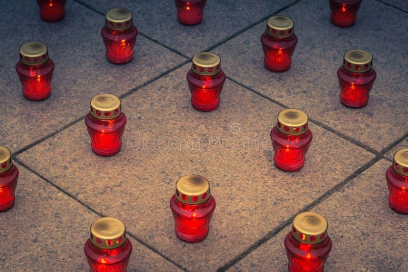 Velas rojas conmemorativas ardientes de la linterna en las losas del granito fotos de archivo libres de regalías