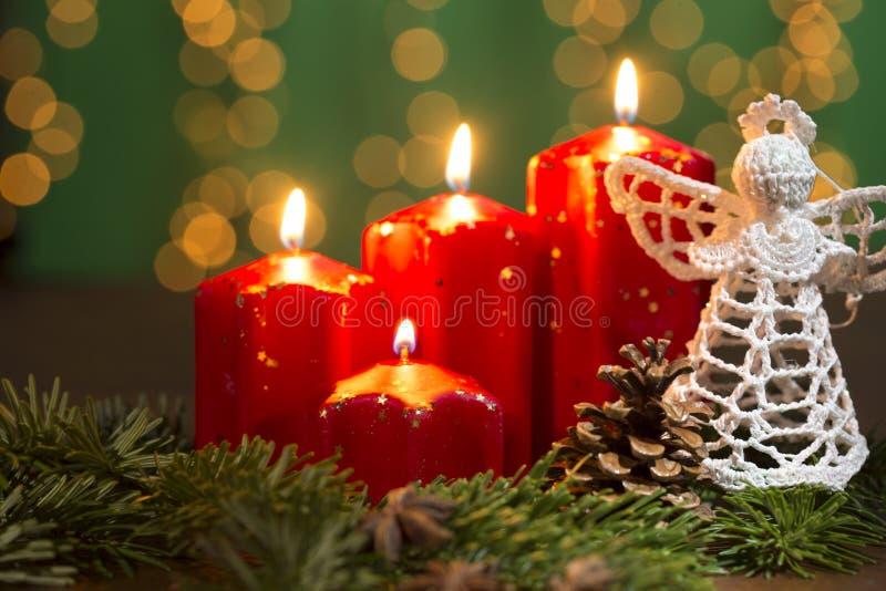 Velas rojas del advenimiento en el viejo fondo de madera con la cortina de la luz de la Navidad fotografía de archivo