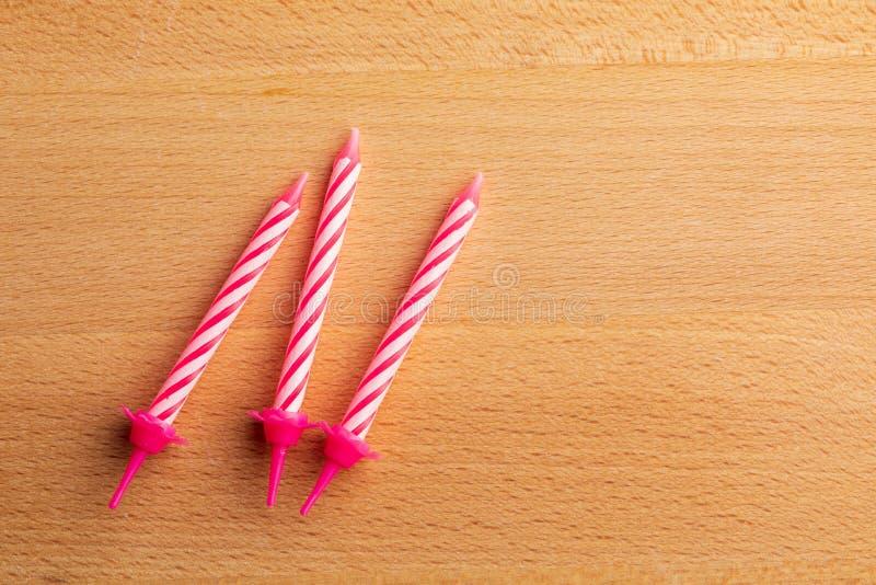 3 velas rosadas del cumpleaños en fondo de madera Para la tarjeta de felicitación del cumpleaños Espacio para insertar el texto fotos de archivo libres de regalías
