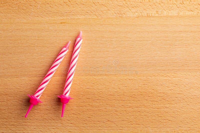 2 velas rosadas del cumpleaños en fondo de madera Para la tarjeta de felicitación del cumpleaños Espacio para insertar el texto imágenes de archivo libres de regalías