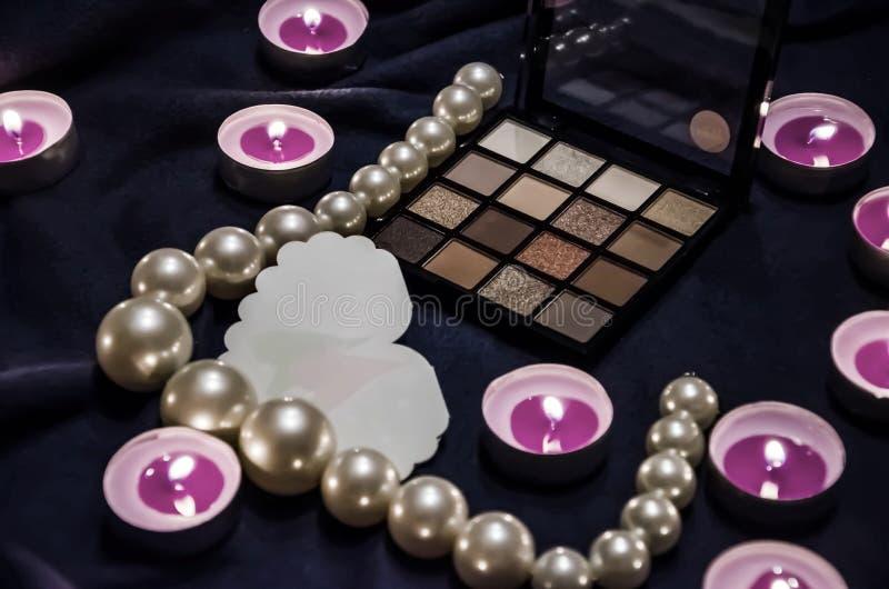 Velas Scented, uma paleta das sombras, um coração e grânulos bonitos em uma cobertura fotos de stock