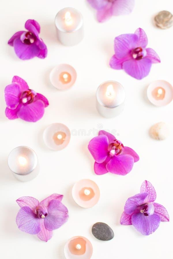 Velas y flores ardientes de la orquídea en fondo de madera Concepto del balneario de la relajación fotos de archivo
