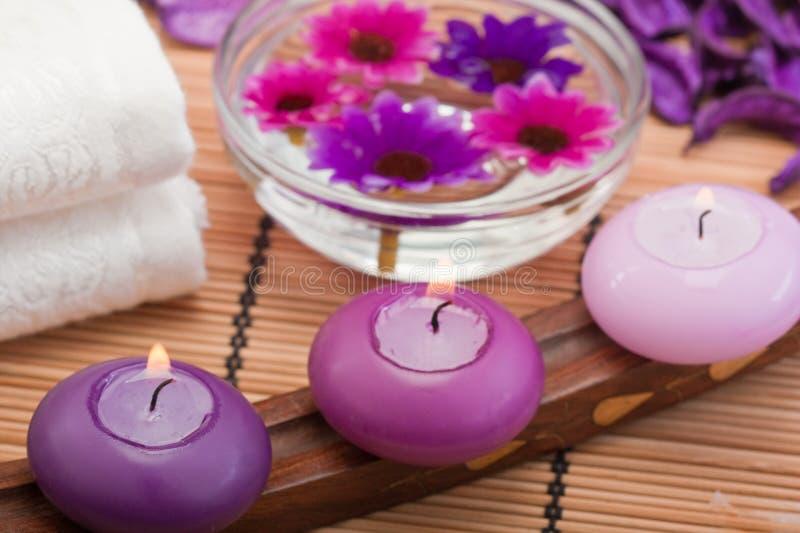Velas y flores púrpuras en la configuración del balneario (2) imagenes de archivo