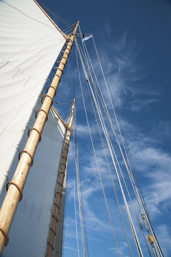 Velas y palos de madera del velero viejo del goleta que alcanza al azul imagen de archivo libre de regalías
