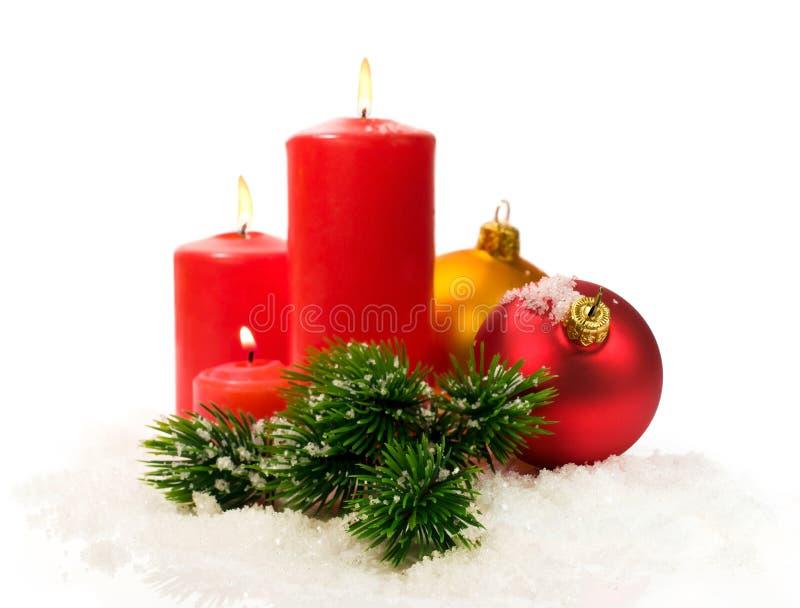 Velas y ramas del abeto y bolas rojas de la Navidad en nieve fotografía de archivo