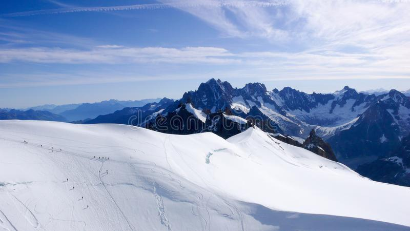 Vele alpinisten die zich als mieren over een grote gletsjer in de Franse Alpen dichtbij CHamonix bewegen stock afbeeldingen