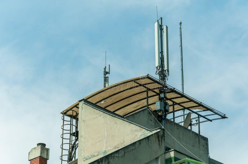Vele antennes van de telefoonontvangers van de telecommunicatiecel op de dakbovenkant van de woningbouw met blauwe hemelachtergro royalty-vrije stock afbeeldingen