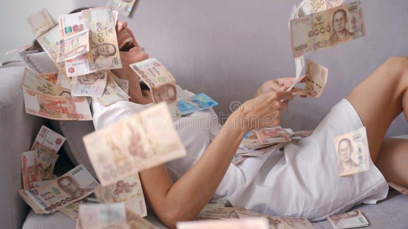 Vele bankbiljetten vliegen boven in de lucht in langzame motie Een meisje ligt en heel wat gelddalingen op haar de gelukkige vrou stock afbeeldingen