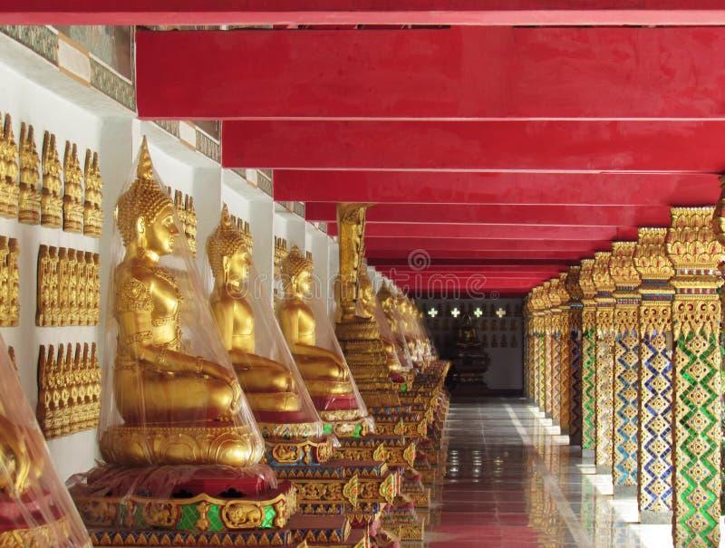 Vele beelden van Boedha zitten op een rij langs de gangen van Boeddhistische tempel in Thailand Beelden van zijaanzicht royalty-vrije stock foto