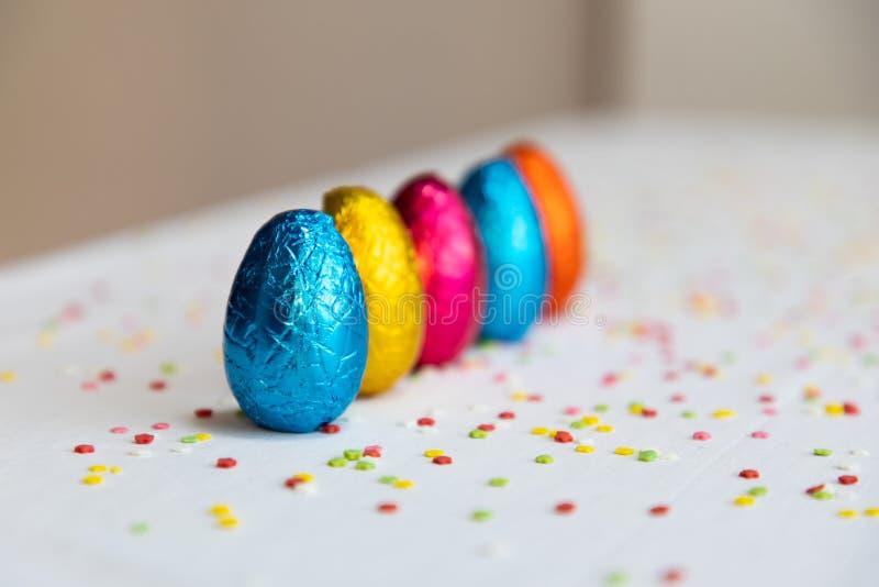 Vele bevindende gekleurde chocoladepaaseieren op witte achtergrond en kleurrijke confettien royalty-vrije stock foto's