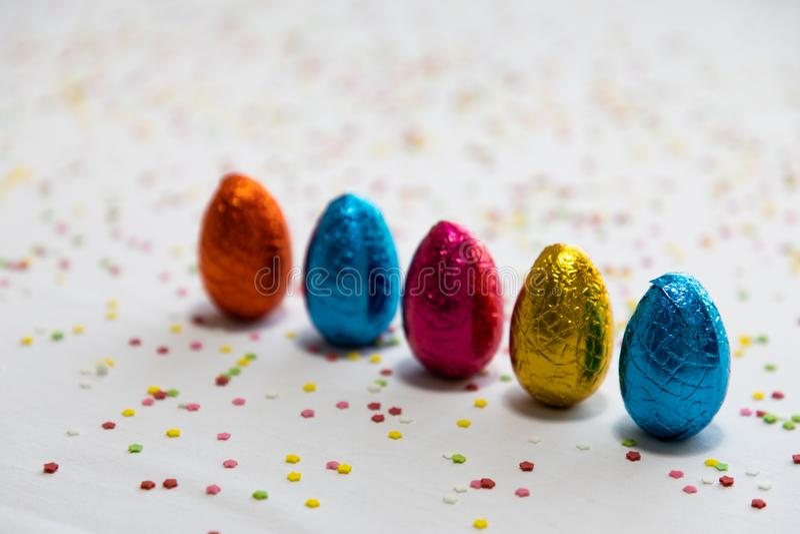 Vele bevindende gekleurde chocoladepaaseieren op witte achtergrond en kleurrijke confettien stock afbeeldingen