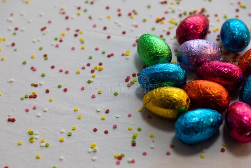 Vele bevindende gekleurde chocoladepaaseieren op witte achtergrond en kleurrijke confettien royalty-vrije stock afbeeldingen