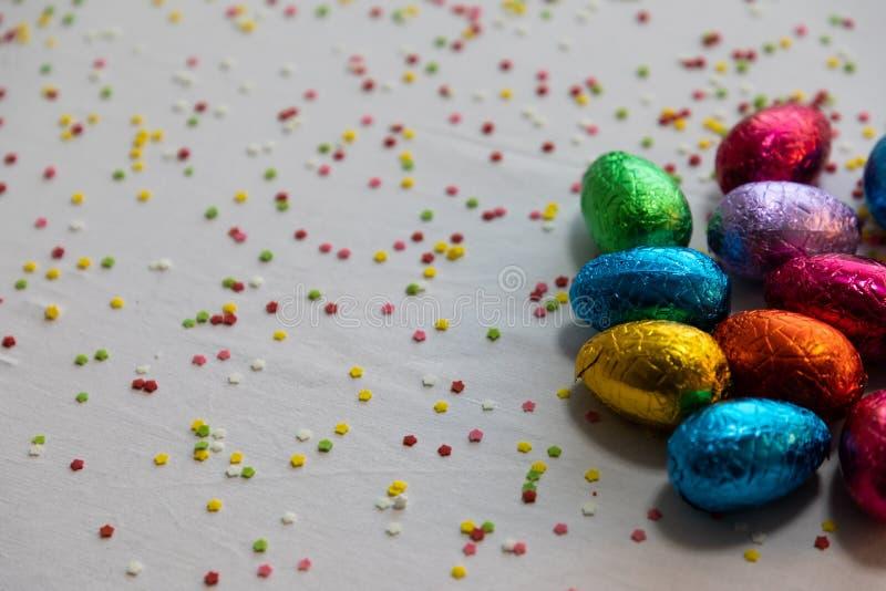 Vele bevindende gekleurde chocoladepaaseieren op witte achtergrond en kleurrijke confettien royalty-vrije stock foto