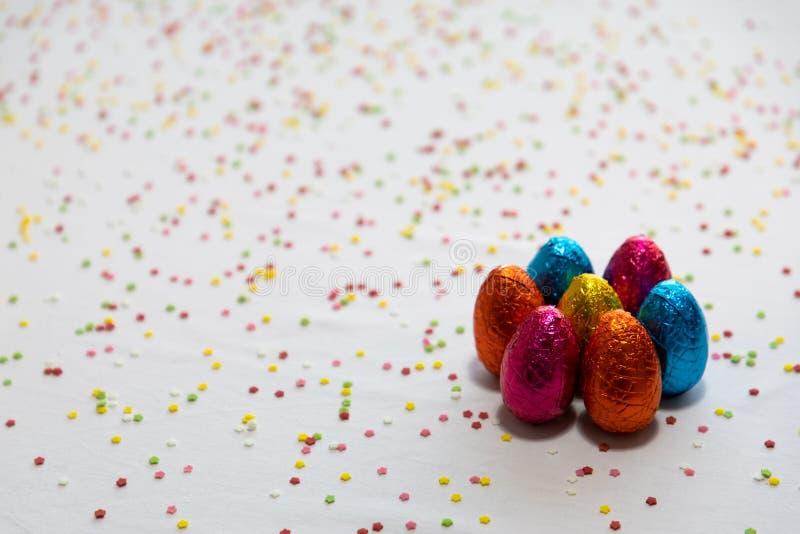 Vele bevindende gekleurde chocoladepaaseieren op witte achtergrond en kleurrijke confettien royalty-vrije stock fotografie