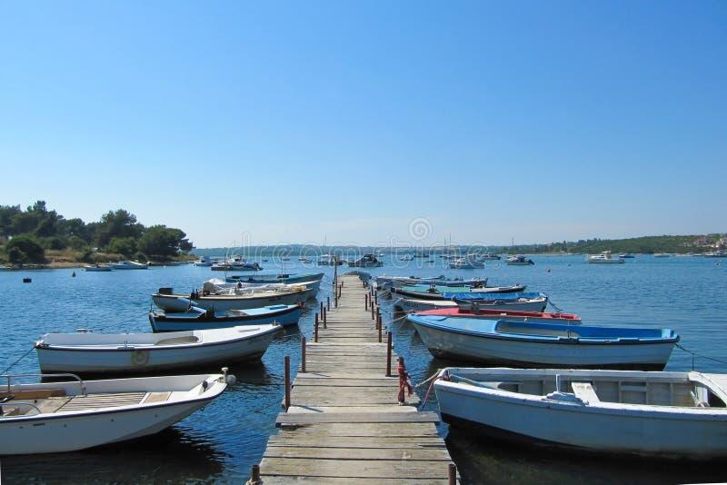 Vele boten bonden aan een houten pijler met een mooie mening van het meer Kroatië, Istra, Medulin - Juli, 2010 stock fotografie