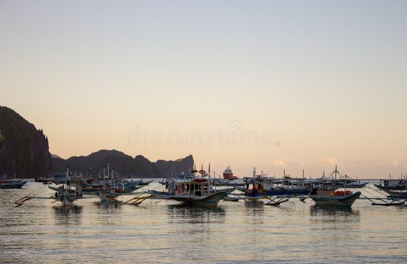 Vele boten in tropische haven in de avond Zonsondergang in lagune in Filippijnen, Palawan, Gr Nido De traditionele zeilboten van  stock afbeelding