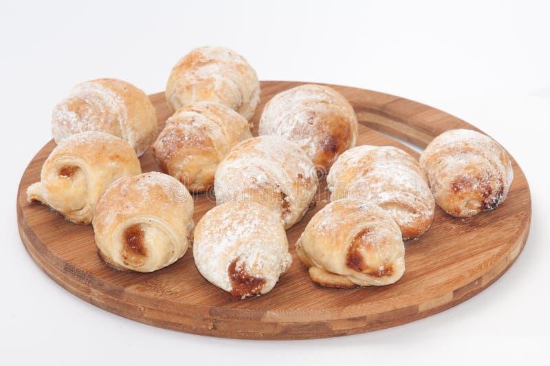 Vele broodjes met jam en bestrooid met poedersuiker op een keuken stock afbeelding