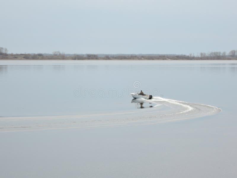 Vele del pescatore sulla barca che affetta attraverso la superficie dell'acqua in molla in anticipo fotografia stock