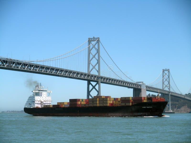 Vele della nave da carico sotto il San Francisco Bay Bridge ed isola un chiaro giorno immagine stock libera da diritti