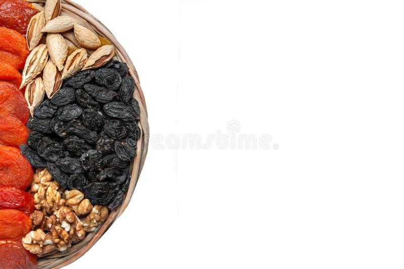 Vele droge vruchten op een ronde houten die plaat, cashewnoten, gedroogde pruimen, fig., rozijn en abrikozen op wit wordt geïsole royalty-vrije stock afbeelding