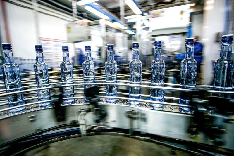 Vele flessen op transportband stock fotografie