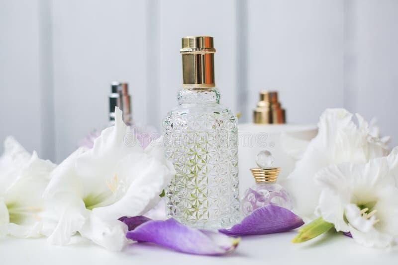 Vele flessen parfum met witte bloemen stock afbeeldingen