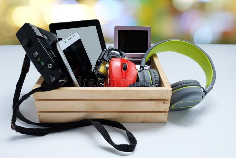 Vele gebruikte moderne Elektronische gadgets voor dagelijks gebruik in houten gevallen op witte achtergrond royalty-vrije stock afbeelding