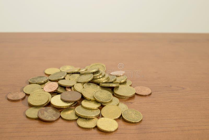 Vele gedetailleerde euro muntstukken op een houten lijst stock afbeeldingen