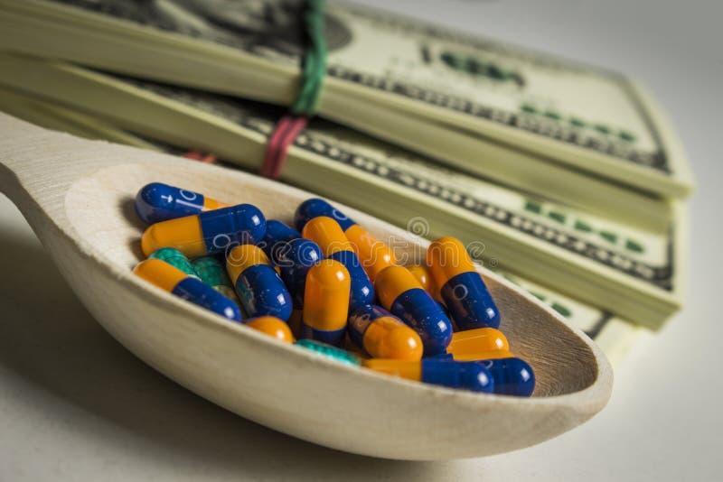 Vele gekleurde capsules in een houten lepel op een lijst met pakken dollars royalty-vrije stock fotografie